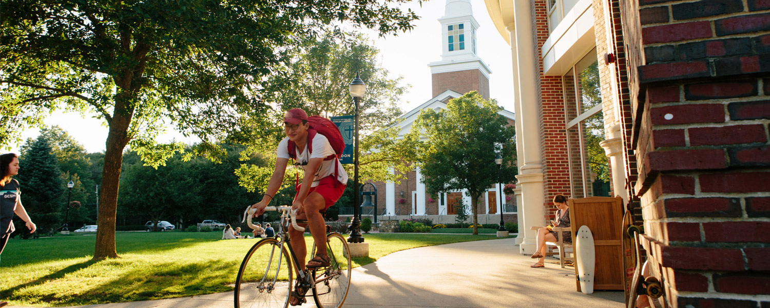 student riding a bike near the chapel