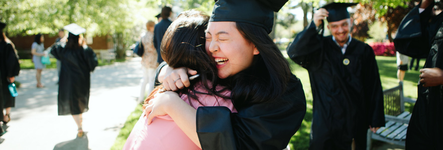 Graduate hugging friend