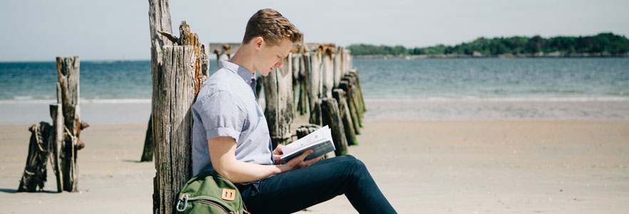 Student reading on the beach