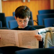 A young boy with sheet music