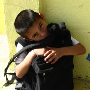 A child at the orphanage with his backpack