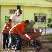 Students placing bricks in a wheelbarrow